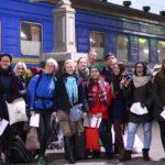 Групове фото учаників проекту на фоні потягу. Всі учасники тримають квитки. На табличці зверху написано: колія №4.