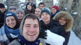 A happy selfie, taken by an international group at the top of the tower. The city is visible in the background. One of the boys is holding a snow lump