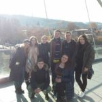 The last group photo before leaving. Everyone is happy. Group of eight people is on the famous Bridge of Peace in Tbilisi. The sun shines bright.