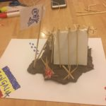 "A tent, a flag and a bonfire made with the modeling clay, paper, sticks and marker placed on the table. There is a skull on the flag and inscription ""Bongalia"" on the blue, yellow and red flag next to the tent."