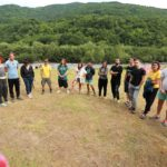 Participants are standing in semi-circle. There is a river and green mountains on the backgrund.