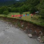 The photo is divided into two parts: on the left there is mountain river, on the right there is a camping place and a lot of green trees around. Small groups of people are standing next to the tents.