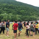 Participants are playing a game on the lawn by the tents and river.All of them are standstill in different poses.