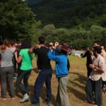 Participants are moving in the circle, doing some exercises with their hands. There are a lot of green trees on the background.
