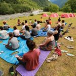 Participants are sitting on mats close to the mountain river, their shoes nearby, their legs crossed. Their palms are on their knees open to the sky. There are blue and red tents on the background.