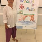 "A woman is standing next to the flipchart with the inscription ""Breathe in Malta"" and picture of the sea and a cliff. She is wearing flip-flops, baggy pants and shirt. There is a phone in her right hand."