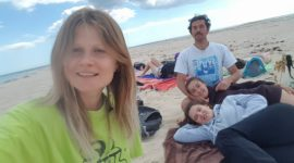 Three girls and one boy are on an almost empty beach. One of the girls is taking a selfie, others are lying on the towel, the boy is sitting next to them.