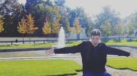 волонтер біля галявини з фонтаном