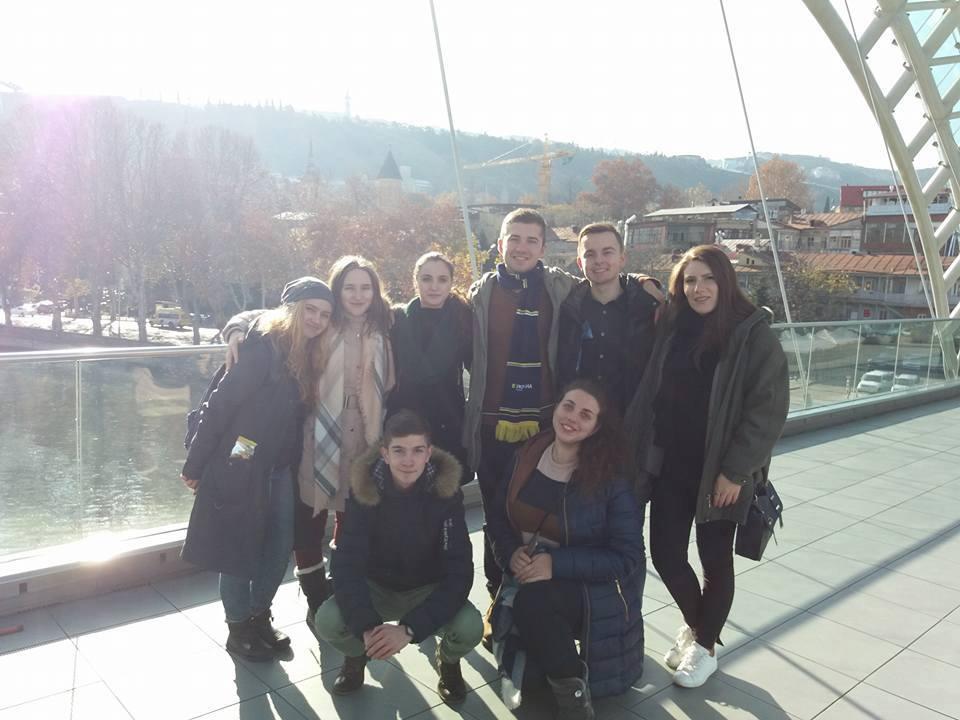 Група з 8 людей стоїть на відомому Мості Миру в Тбілісі. Яскраво світить сонце.