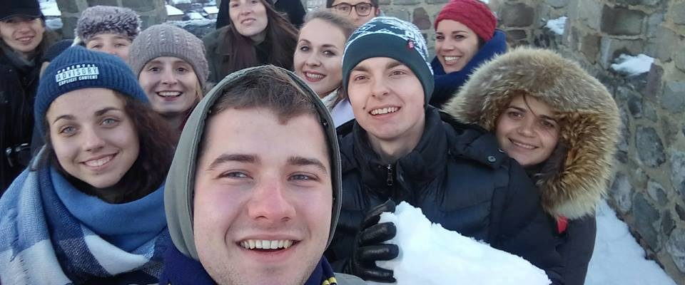 A happy selfie, taken by an international group at the top of the tower. The city is visible in the background. One of the boys is holding a snow lump.