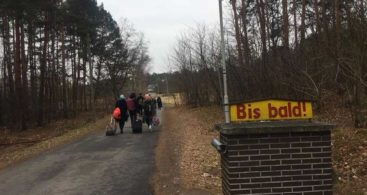 "Participants of the project walk along the road in the wood, only their backs are visible. The sign in the foreground says ""Bis bald!"" which means ""See you soon!""."