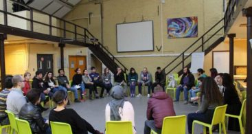 Participants sit in the circle and look at the trainer. There is a flipchart and multimedia projector screen in the backgroud.