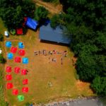 "Photo is taken from the sky. On the left there is a camp with blue and red tents, there is one yellow tent. On the right there is a huge tent and next to it there is an inscription ""Breathe in!"" made with participants' bodies. The territory is surrounded by trees."