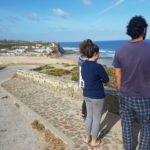 Three people are standing next to the road gazing at the sea. There is a town on the background.