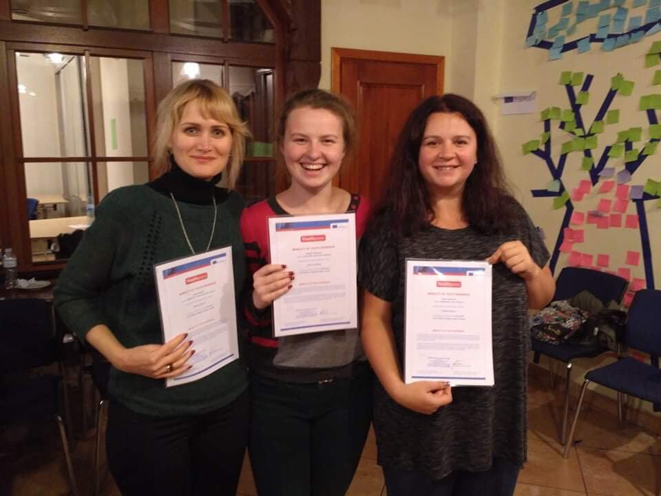 Three girls are standing next to each other, smiling and holding certificates in their hands